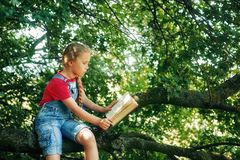 Little blonde girl with a book on a tree . royalty free stock photography