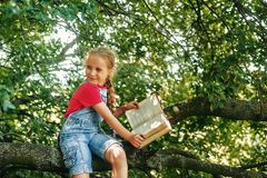 Little blonde girl with a book on a tree . royalty free stock photos