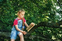 Little blonde girl with a book on a tree . royalty free stock images