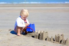 Little blonde girl building sand castles on the beach Royalty Free Stock Image