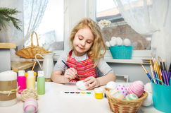Little blonde girl coloring eggs for Easter holiday at home Royalty Free Stock Photo