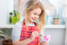 Little blonde girl coloring eggs for Easter holiday at home Stock Photo
