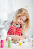 Little blonde girl coloring eggs for Easter holiday at home Stock Image