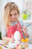 Little blonde girl coloring eggs for Easter holiday at home Royalty Free Stock Photography