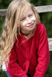 Little blonde girl with curly long hair, portrait, in a red sweater in the sun stock photo