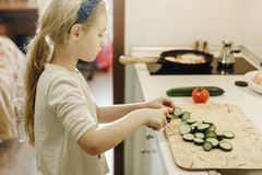 Little blonde girl cutting vegetables while cooking in kitchen at home stock images