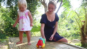 Little blonde girl dance near her mother under tropical trees at sunrise. Little blonde girl dancing and takes small toy car near her mother sitting under stock video