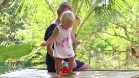 Little blonde girl dance near her mother under tropical trees at sunrise. Little blonde girl dancing and takes small toy car near her mother sitting under stock video footage