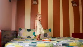 little blonde girl dances with joy around new toy on sofa stock footage