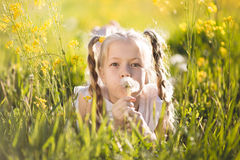 Little blonde girl with dandelion flower Stock Photos