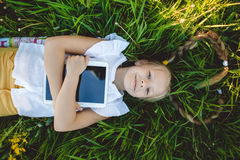 Little blonde girl with digital tablet. Little cute blonde girl is lying on back with digital tablet in yellow field with flowers stock photos