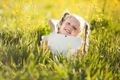 Little blonde girl with digital tablet on the nature stock photography