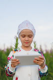 Little blonde girl with digital tablet on the nature Stock Images