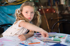 Little blonde girl drawing with crayons outdoors Stock Image