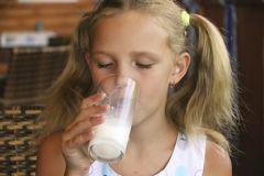Little blonde girl drinks milk in cafe Royalty Free Stock Image