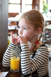 Little blonde girl drinks orange juice using drinking straw Stock Photos