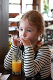 Little blonde girl drinks orange juice using drinking straw Stock Photo