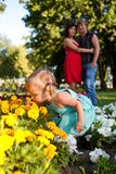 Little blonde girl and flowers. Behind her are the happy parents. Selective focus on baby Stock Photos