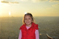 Little blonde girl in front of foggy and misty views of the city Royalty Free Stock Image