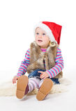 Little blonde girl in a fur jacket and a red Santa's cap sits on Stock Photography