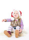 Little blonde girl in a fur jacket and a red Santa's cap Stock Image