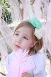 Little blonde girl with a green flower headband and pink feather Royalty Free Stock Photography