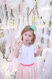 Little blonde girl with a green flower headband and pink feather Royalty Free Stock Photo