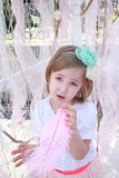 Little blonde girl with a green flower headband and pink feather Stock Photo