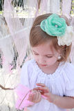 Little blonde girl with a green flower headband and pink feather Stock Images