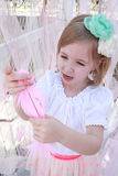 Little blonde girl with a green flower headband and pink feather Stock Photography