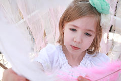 Little blonde girl with a green flower headband and pink feather Royalty Free Stock Photos