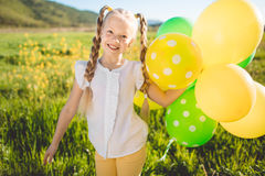 Little blonde girl with green and yellow balloons Royalty Free Stock Photo