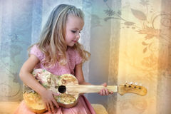 Little blonde girl  with a guitar in vintage style Stock Photo