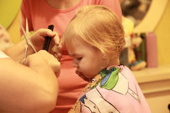 Little blonde girl in hairdressing beauty salon. Royalty Free Stock Images
