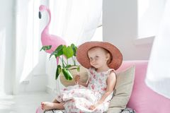 Little blonde girl in hat sitting on a couch in her room. Small girl and pink flamingo indoors.  royalty free stock image