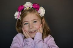 Little blonde girl with her hands on her cheeks Royalty Free Stock Images