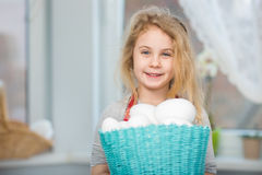 Little blonde girl holding basket with painted eggs. Easter day. Stock Images