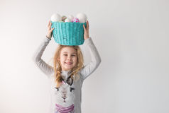 Little blonde girl holding basket with painted eggs. Easter day. Royalty Free Stock Image