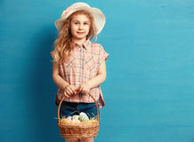 Little blonde girl holding basket with painted eggs. Easter day. Royalty Free Stock Photo
