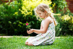 Little blonde girl holding young flower plant in hands on green background. stock image