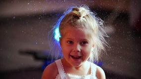 A little blonde girl is inside a huge bubble and expresses delight. Children`s holiday. Close up stock video footage