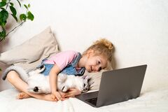 A little blonde girl lies at home on the bed in front of a laptop with a white cat, a place for text, the concept of love for