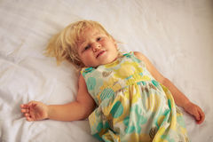 little blonde girl lies on white blanket of sofa Stock Photo