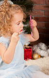 Little blonde girl with lipstick and mirror Royalty Free Stock Photography