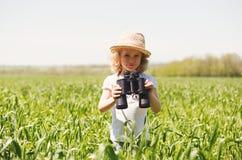 Little blonde girl in looking through binoculars Stock Photos