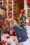 Little blonde girl looking at holiday lights and decorations - v royalty free stock photography
