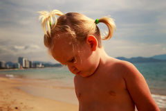 Little blonde girl looks down at beach against resort city Royalty Free Stock Image