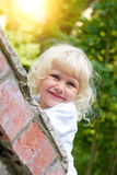 Little blonde girl looks out on street Stock Photos
