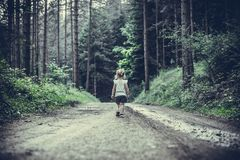 Little Girl Lost in Forest Walking Alone. Little blonde girl lost in forest walking alone on a muddy road with trees in background royalty free stock images