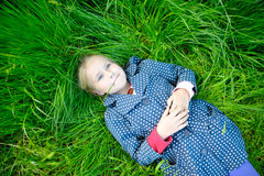 Little blonde girl lying on the grass and dreaming. Little girl lying on the grass in the park, dreaming of something Stock Image
